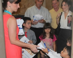 A young boy hands petitions to a representative from Olens' office. (photo by Patrick Saunders)