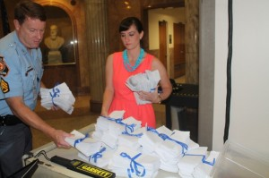 A security guard helps Olens' rep gather up the 3,080 petitions.